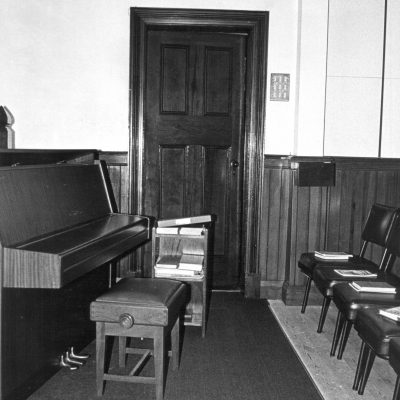 The piano and door to the Prayer Room in the original (extended) building